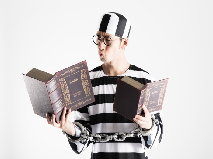 六法全書を片手に勉強する囚人